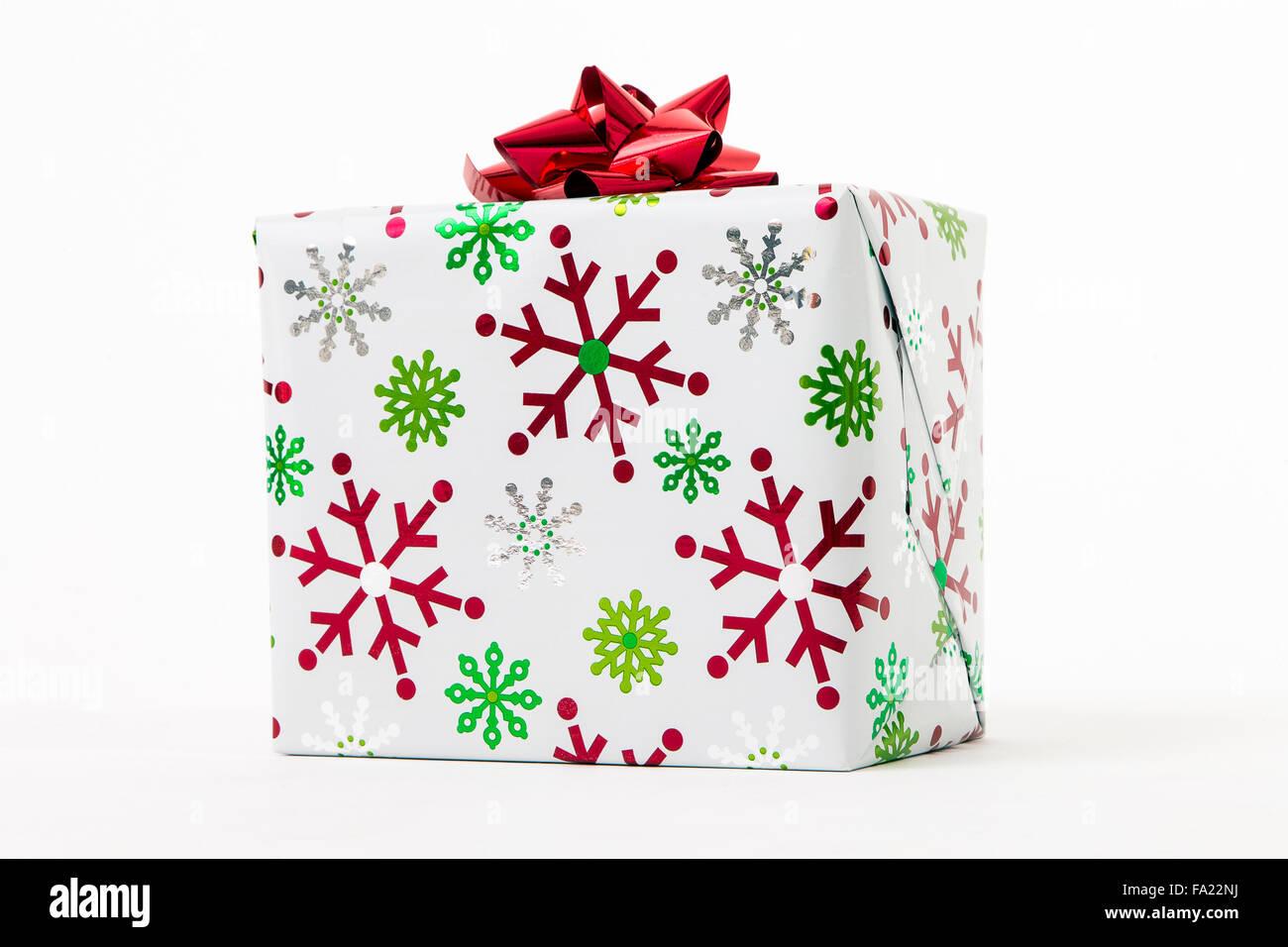 Weihnachtsgeschenk, eingewickelt in Papier mit Schneeflocken Stockbild