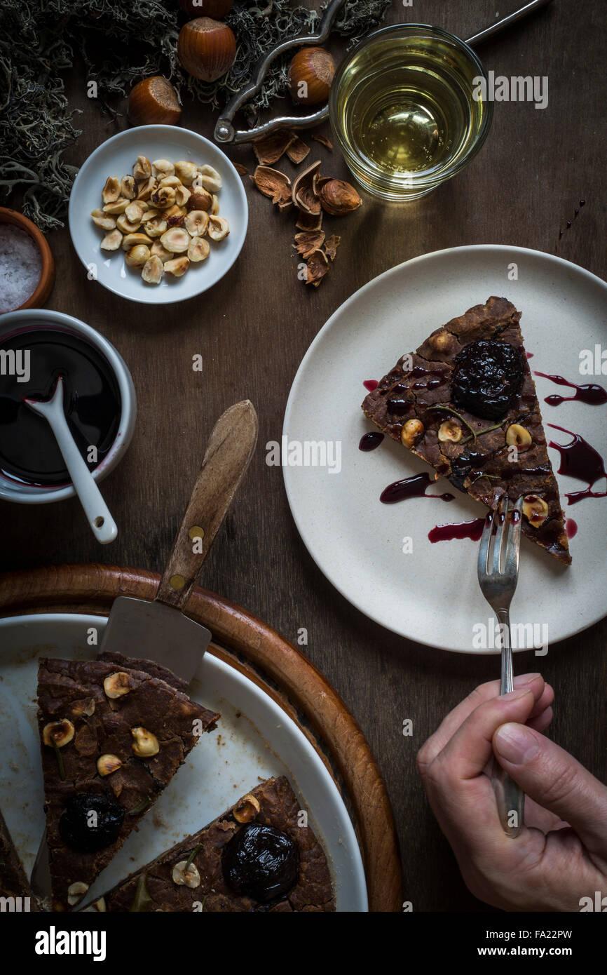 Person Essen ein Stück einer festlichen Mittelmeer Kastanien Mehl Kuchen am Set Holztisch mit Zutaten, Weihnachtsdekoration, Stockbild