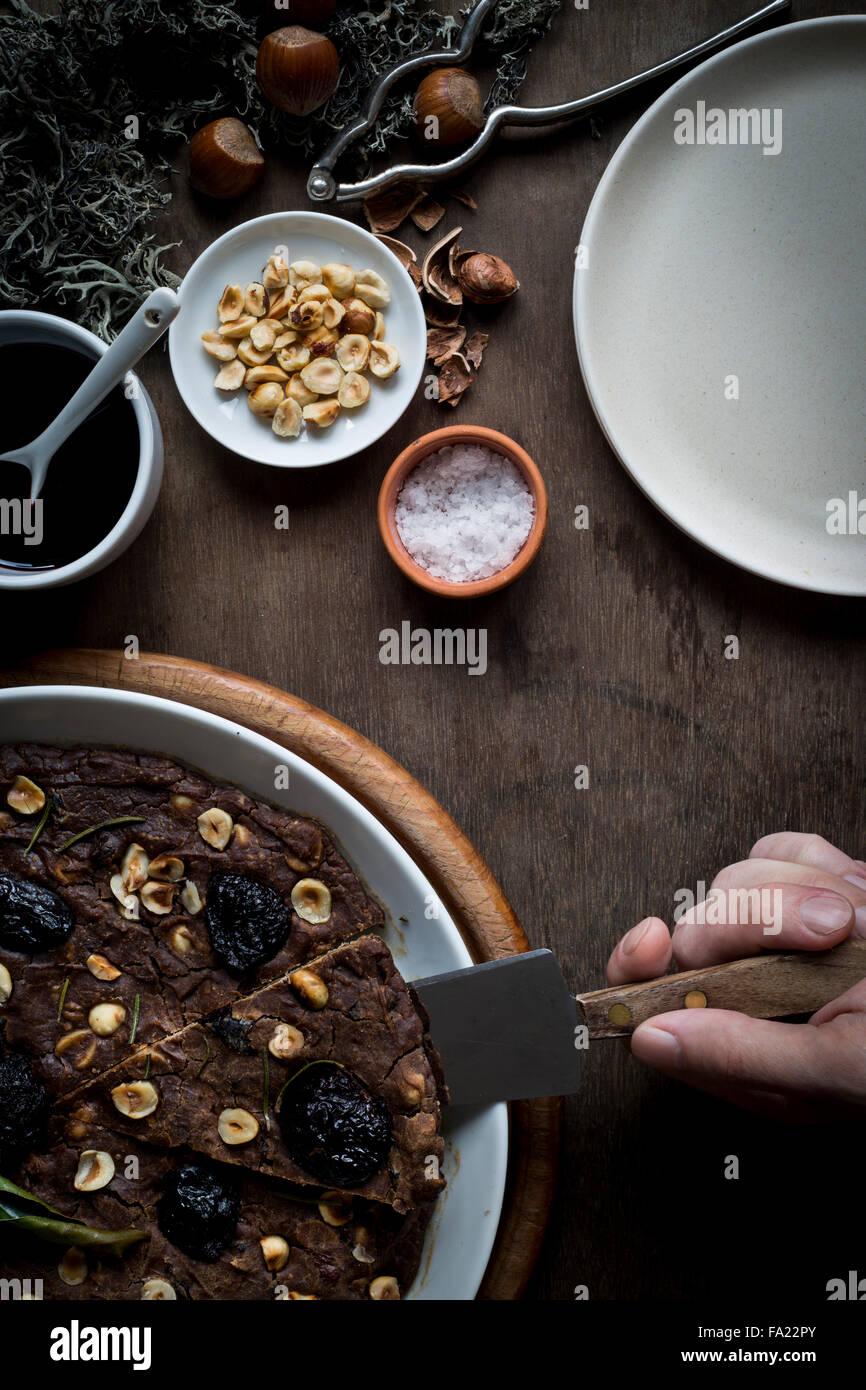 Person auf einer festlichen Mittelmeer Kastanien Mehl Kuchen in weiße Schale schneiden setzen Holztisch mit Stockbild