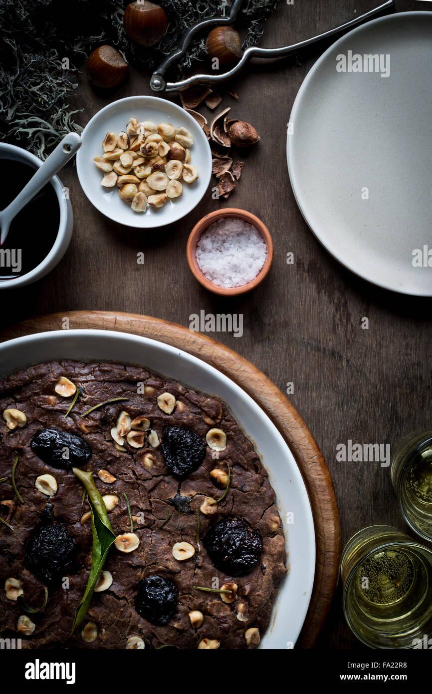 Festliche Mittelmeer Kastanien Mehl Kuchen in weiße Schale auf Set Holztisch mit Zutaten, Weihnachtsdekoration Stockbild