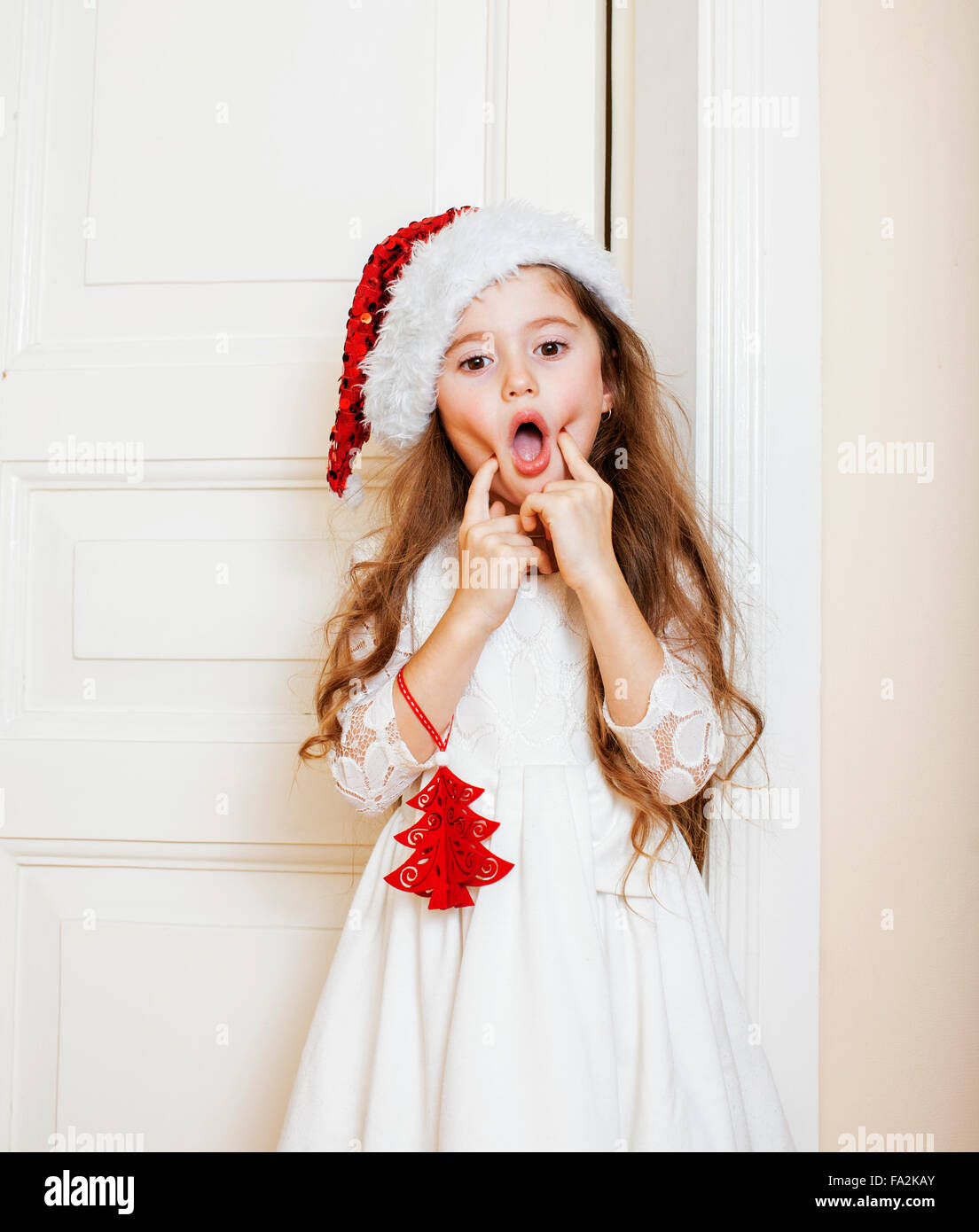 kleine süße Mädchen in Santas roten Hut Weihnachtsgeschenke warten ...