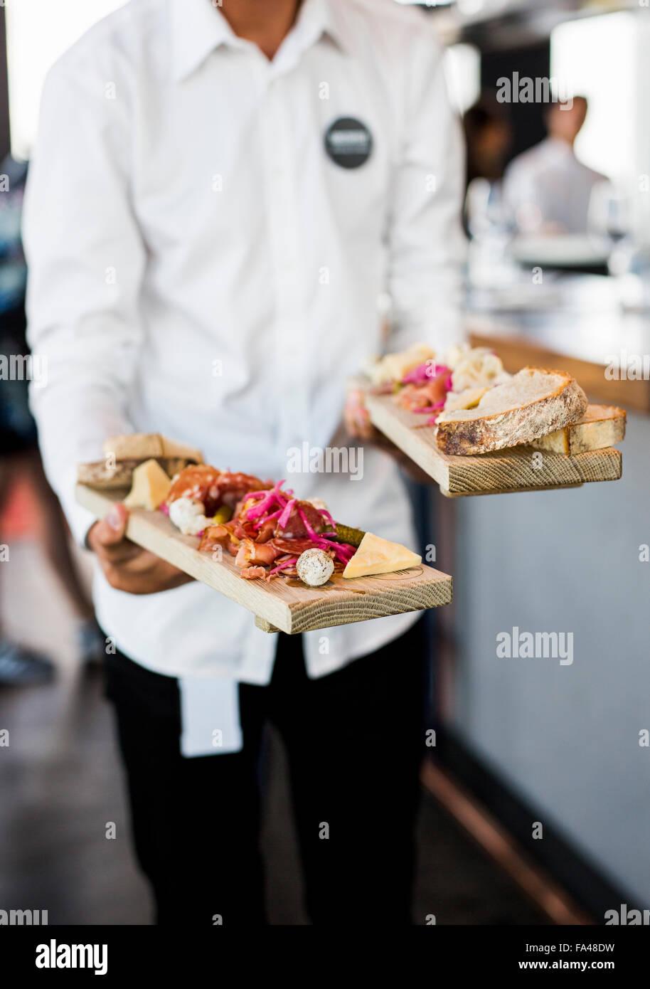Mittelteil der Kellner mit Schüsseln Skybar Restaurant Stockbild