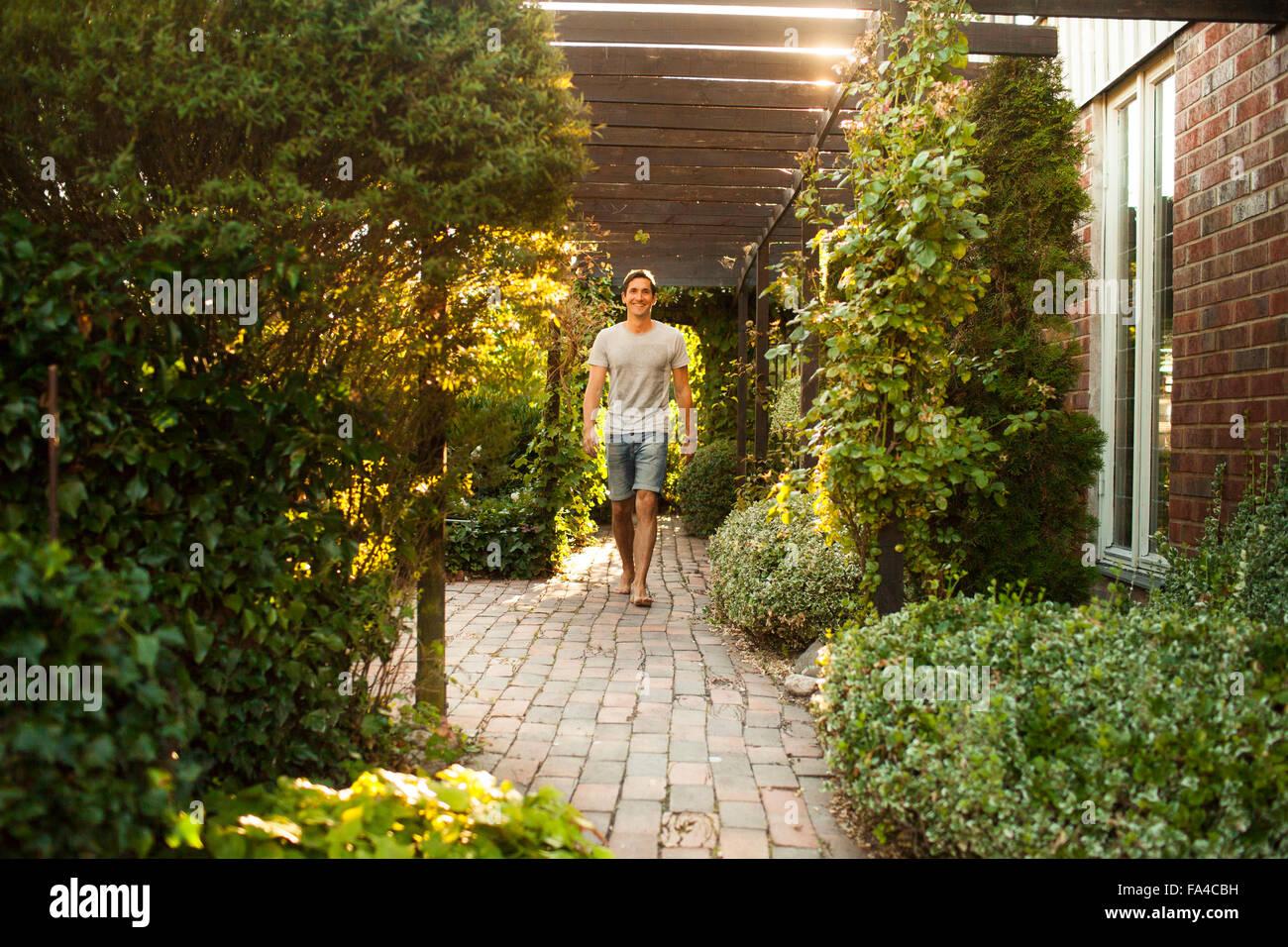 In voller Länge Portrait von glücklich reifer Mann zu Fuß im Hinterhof Stockbild