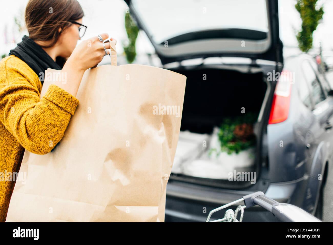 Junge Frau, die Einkaufstasche in den Kofferraum des Autos geladen Stockbild