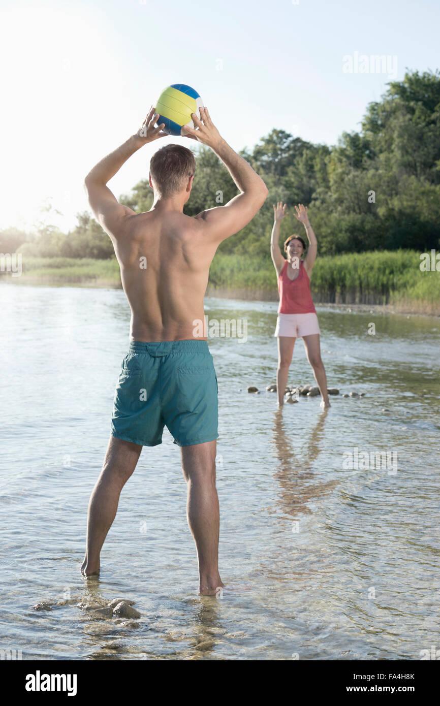 Älteres Paar spielen Sie Volleyball am See, Bayern, Deutschland Stockbild