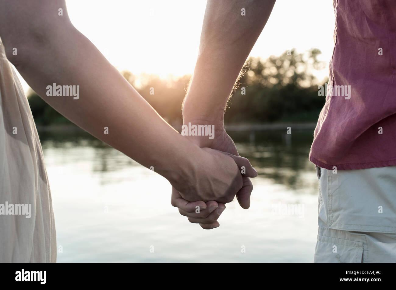 Hand in Hand Mitte Schnittansicht des ein Liebespaar bei Sonnenuntergang, Bayern, Deutschland Stockbild