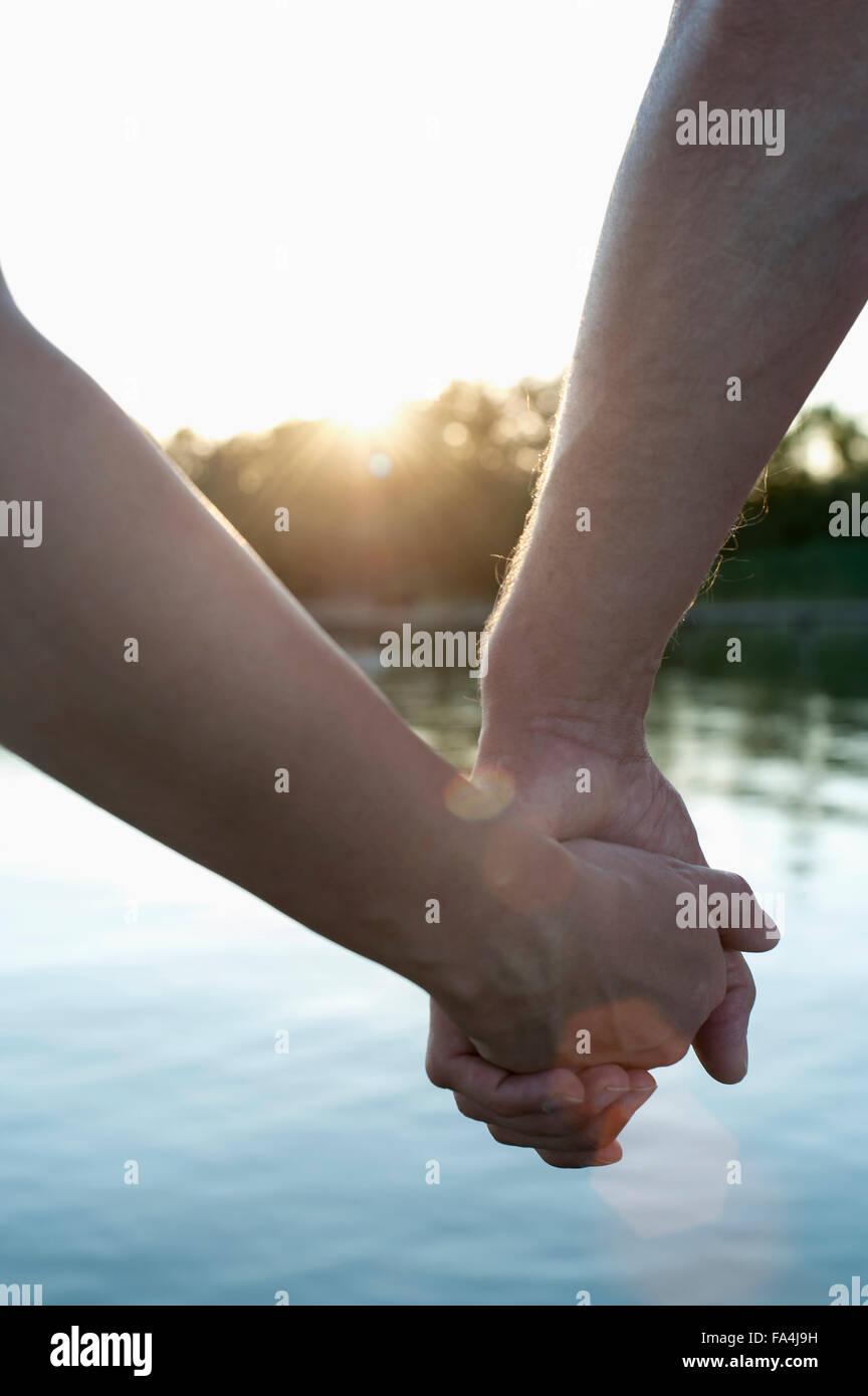 Nahaufnahme des Paares in der Liebe Hand in Hand bei Sonnenuntergang, Bayern, Deutschland Stockbild