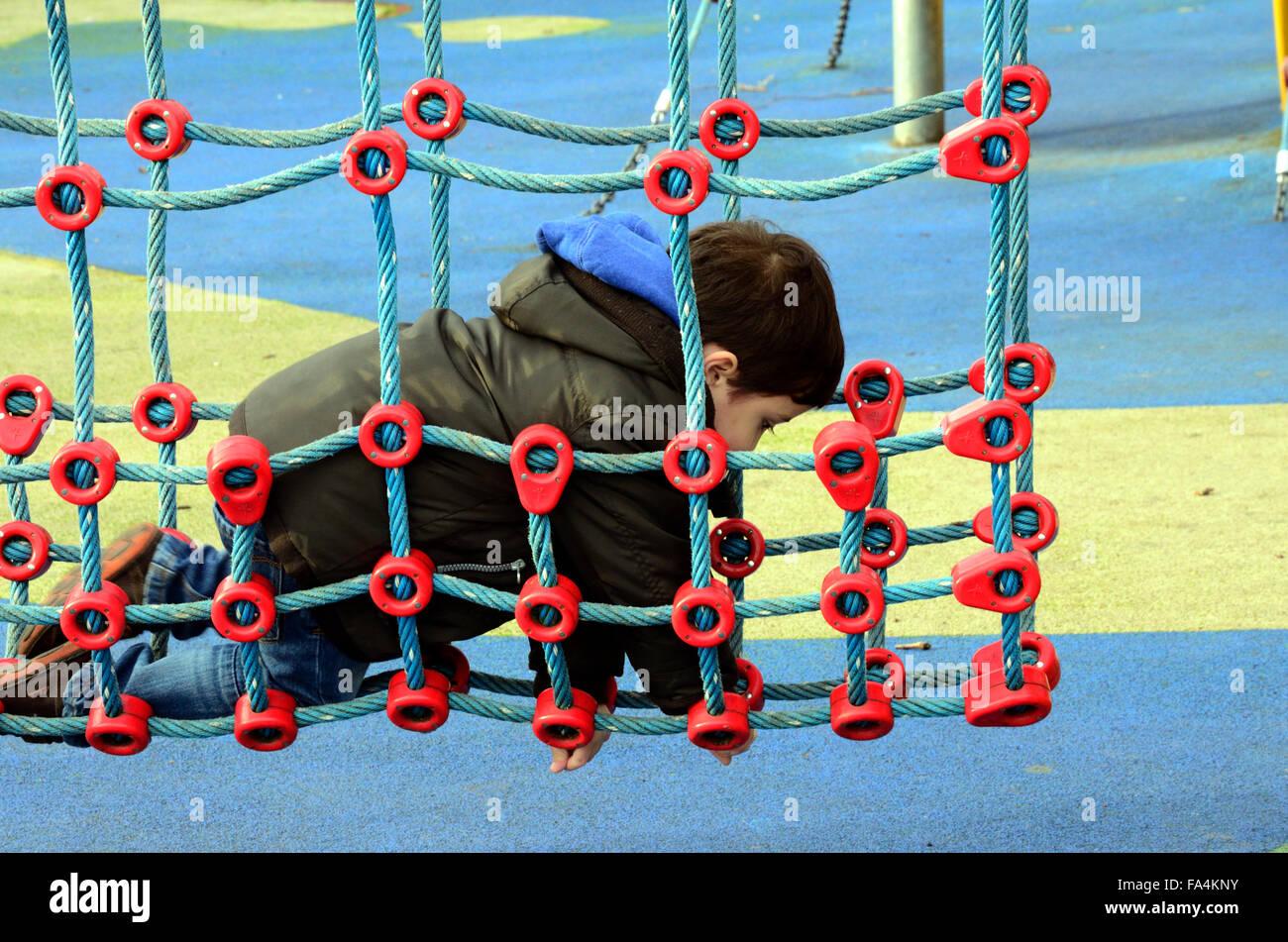 Klettergerüst Mit Netz : Ein kleiner junge spielt auf netz klettergerüst in