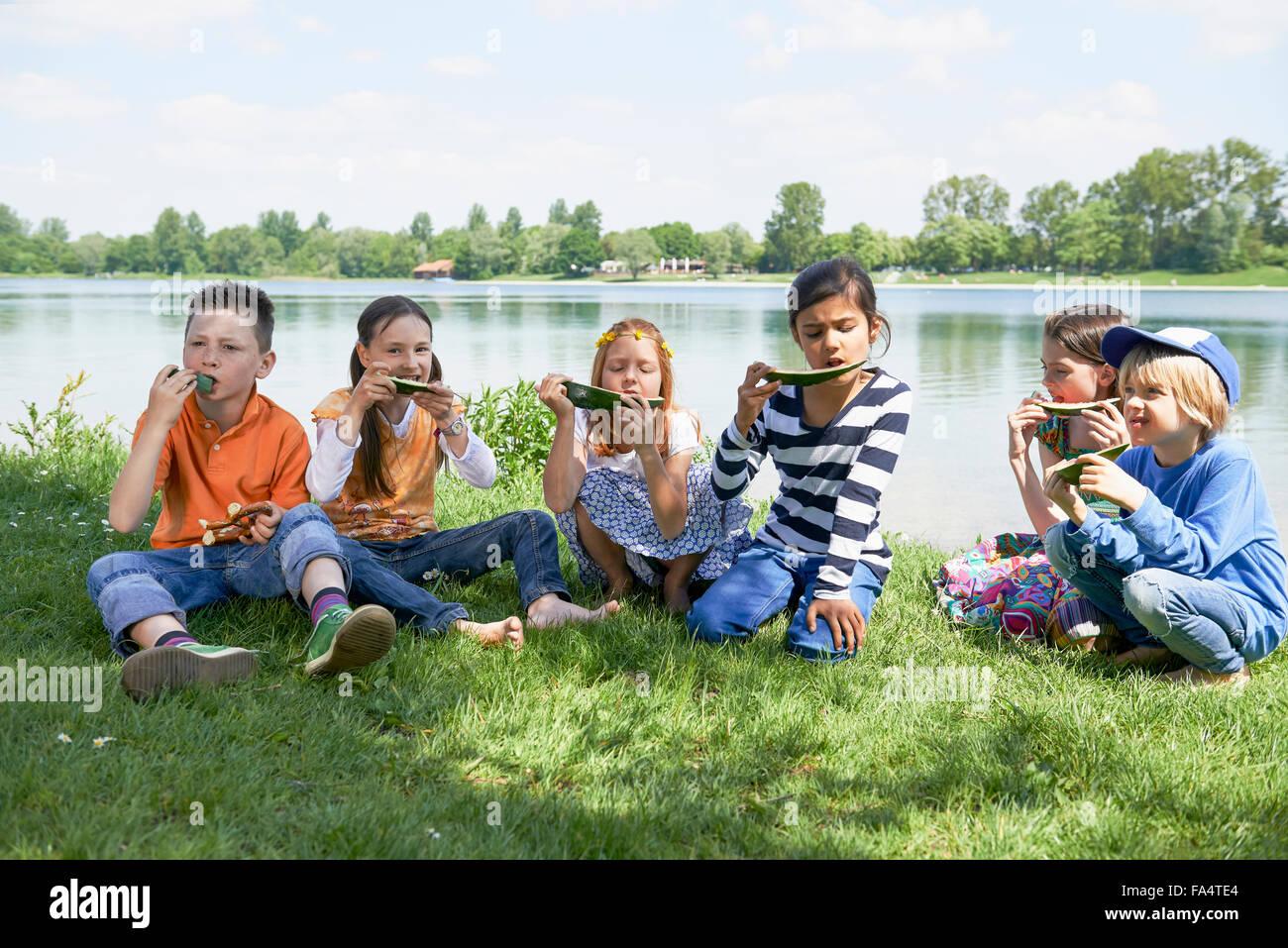 Kinder freuen sich über Scheiben Wassermelone bei Picknick, München, Bayern, Deutschland Stockbild