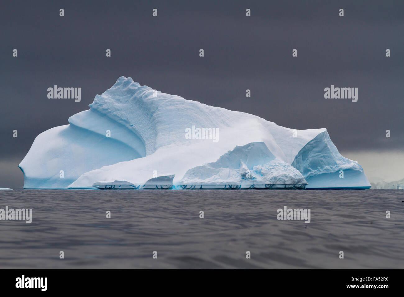 Dramatische Eisberg gegen ein stimmungsvoller Himmel in den antarktischen Ozean Stockbild