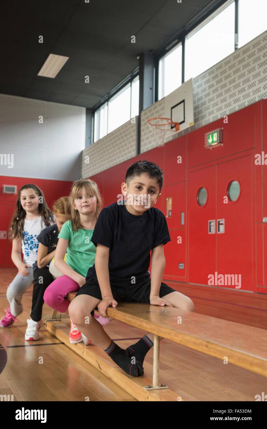 Kinder sitzen auf der Bank im Sport Hall, Bayern, München, Deutschland Stockbild