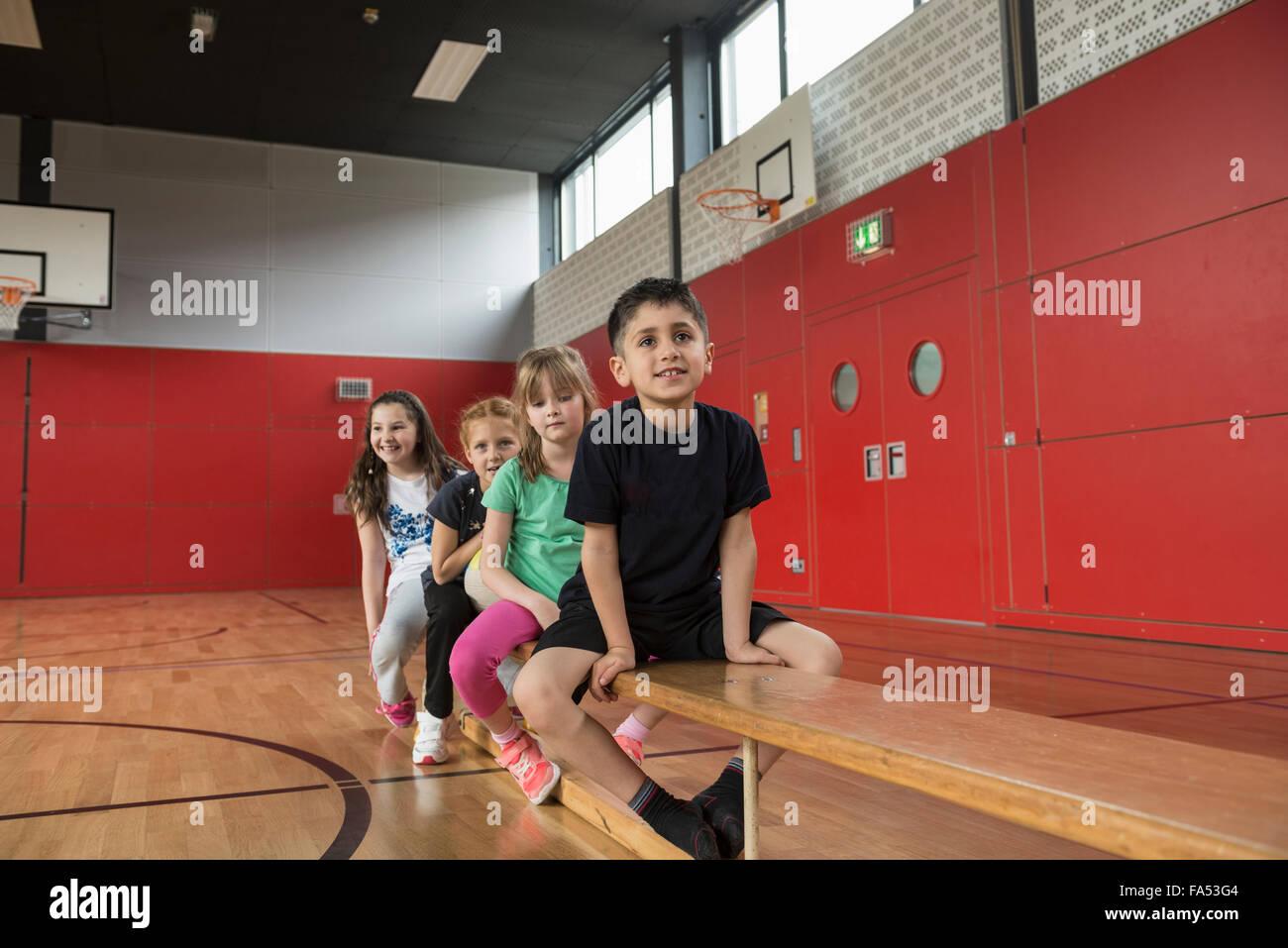 Kinder auf Bank vor Übungen in großen Turnhalle der Schule, Bayern, München, Deutschland Stockbild