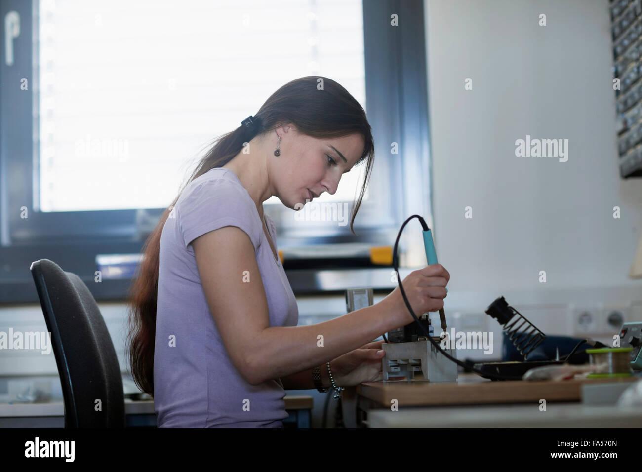 Weiblichen Techniker Löten elektronischer Bauteile in einer Industrieanlage, Freiburg Im Breisgau, Baden-Württemberg, Stockbild