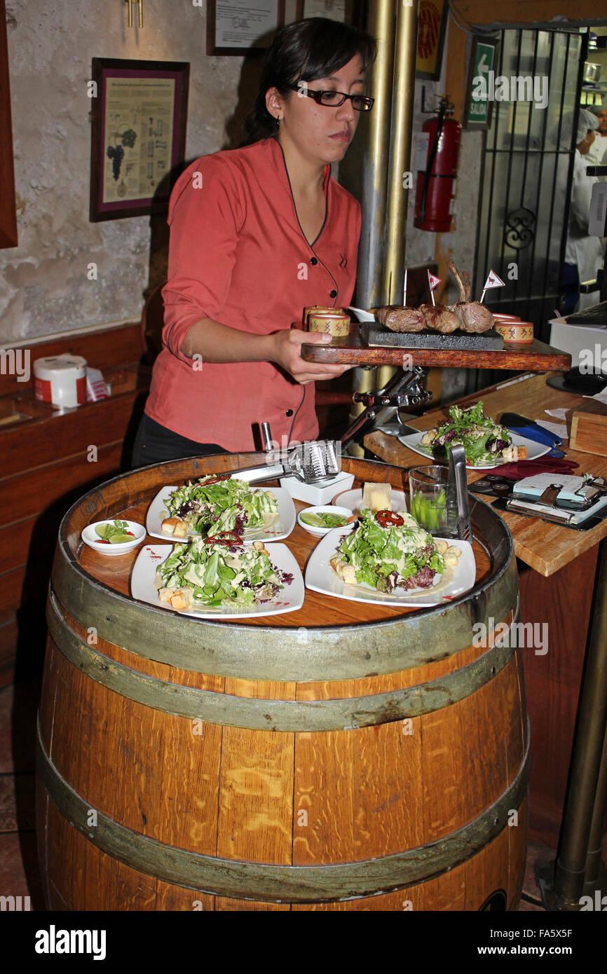 Kellnerin in einem typischen peruanischen Restaurant servieren Platte mit Fleisch und frische Ensalada Stockbild