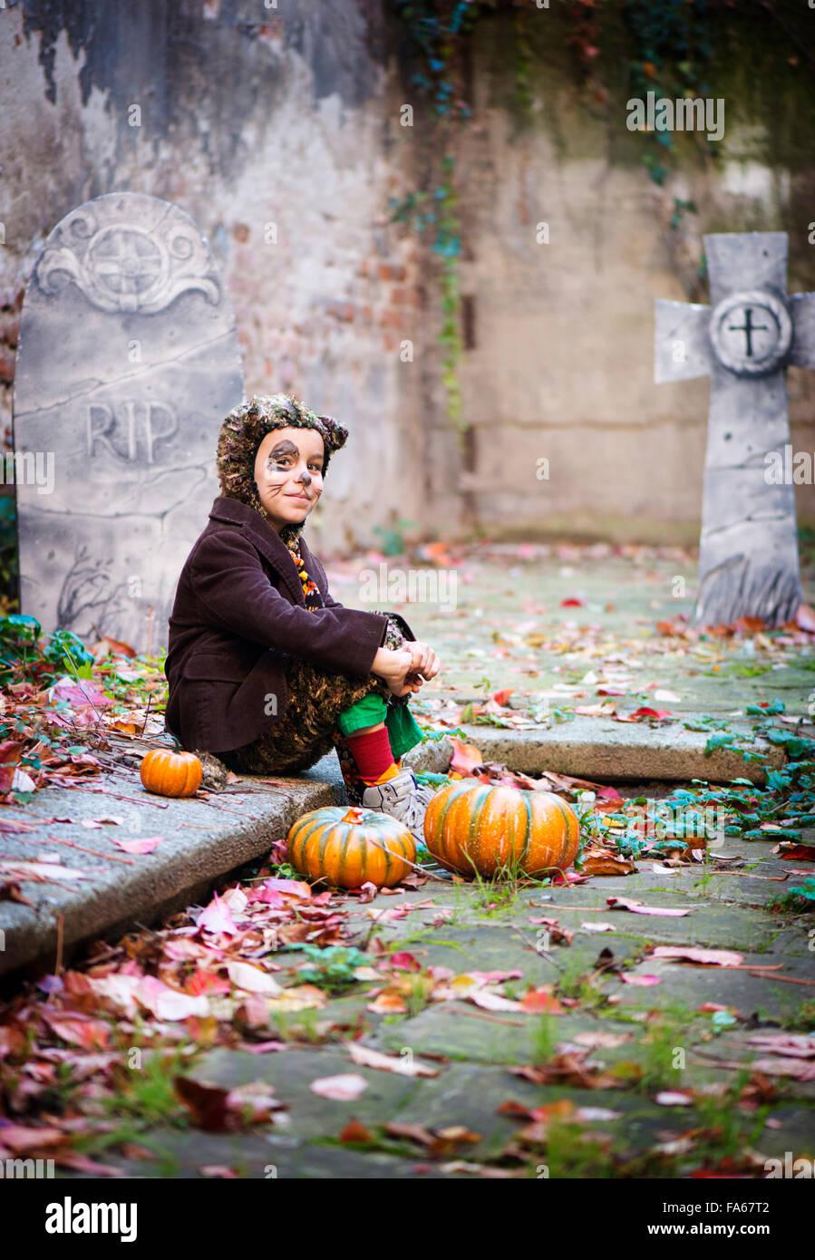 Junge im Halloween-Kostüm sitzen im Friedhof Stockbild