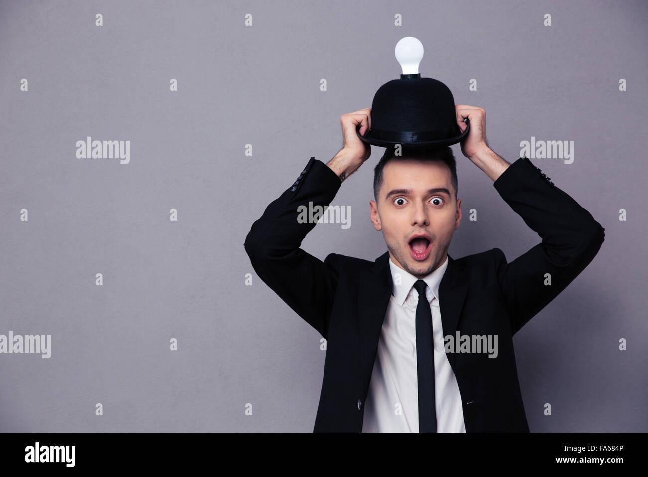 Konzept-Foto eines Geschäftsmannes, eine Vorstellung über den grauen Hintergrund Stockbild