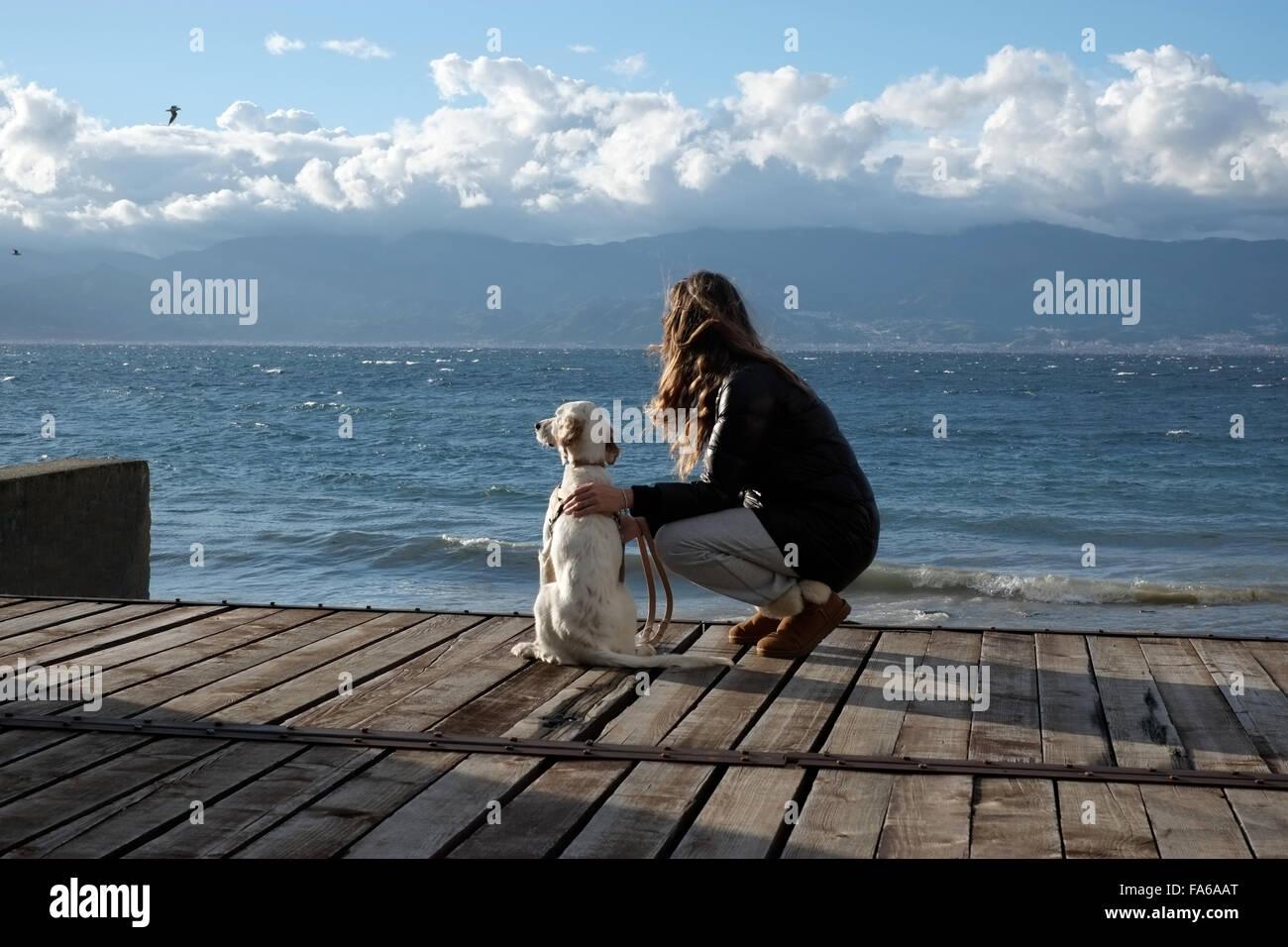 Frau auf dem Seeweg hocken neben ihrem Hund, Reggio Di Calabria, Italien Stockbild