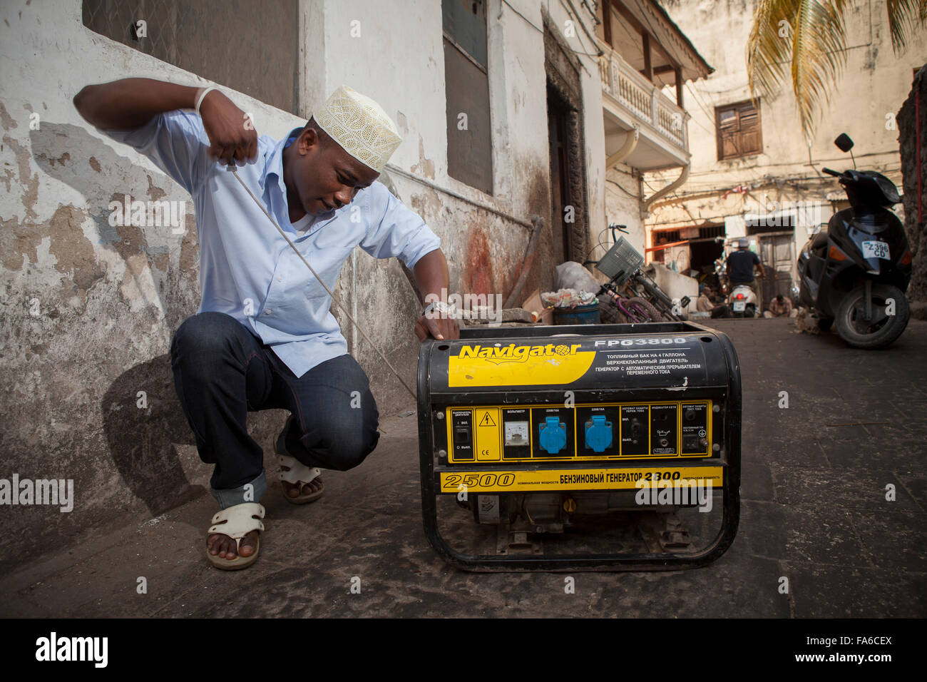 Restaurant-Besitzer Hamisi Saleh Lukmaan startet einen Generator bei einem Stromausfall in Stonetown, Zanzibar, Stockbild