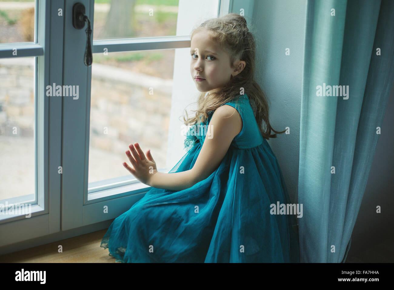 Trauriges Mädchen Blick durch Fenster Stockbild