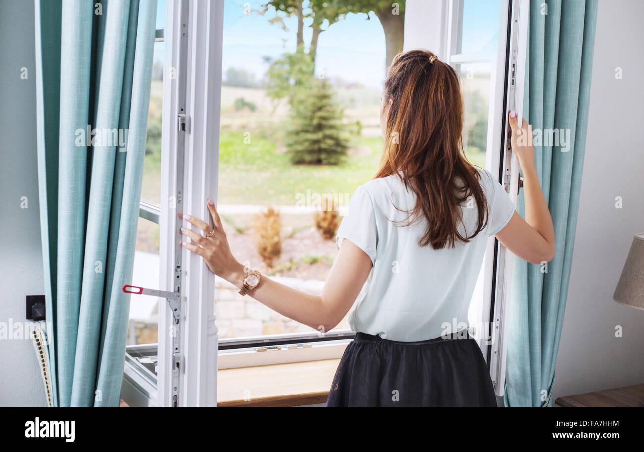 Elegante Dame, die das Schlafzimmerfenster öffnen Stockbild