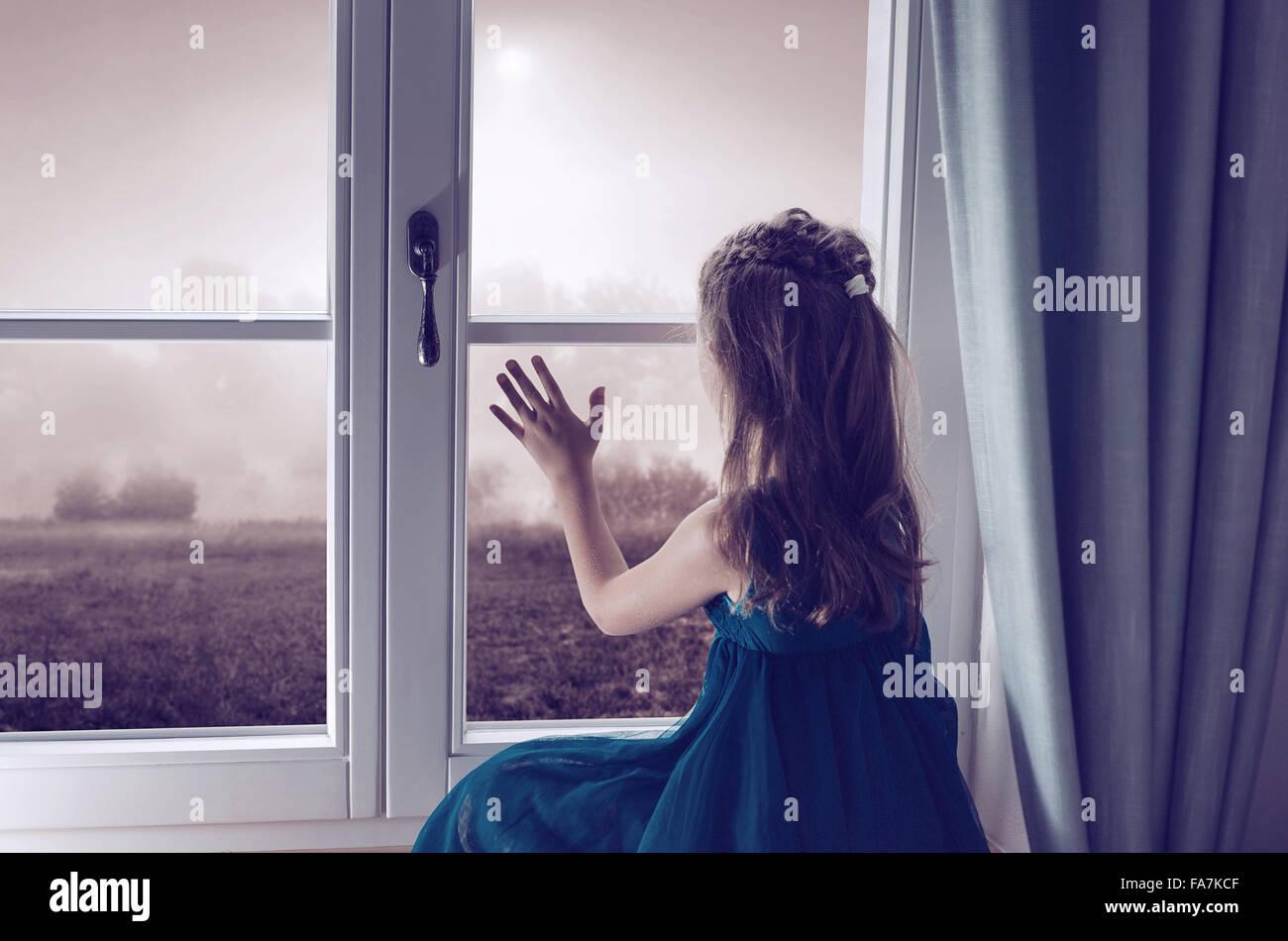 Miserable Kind Blick durch Fenster Stockbild
