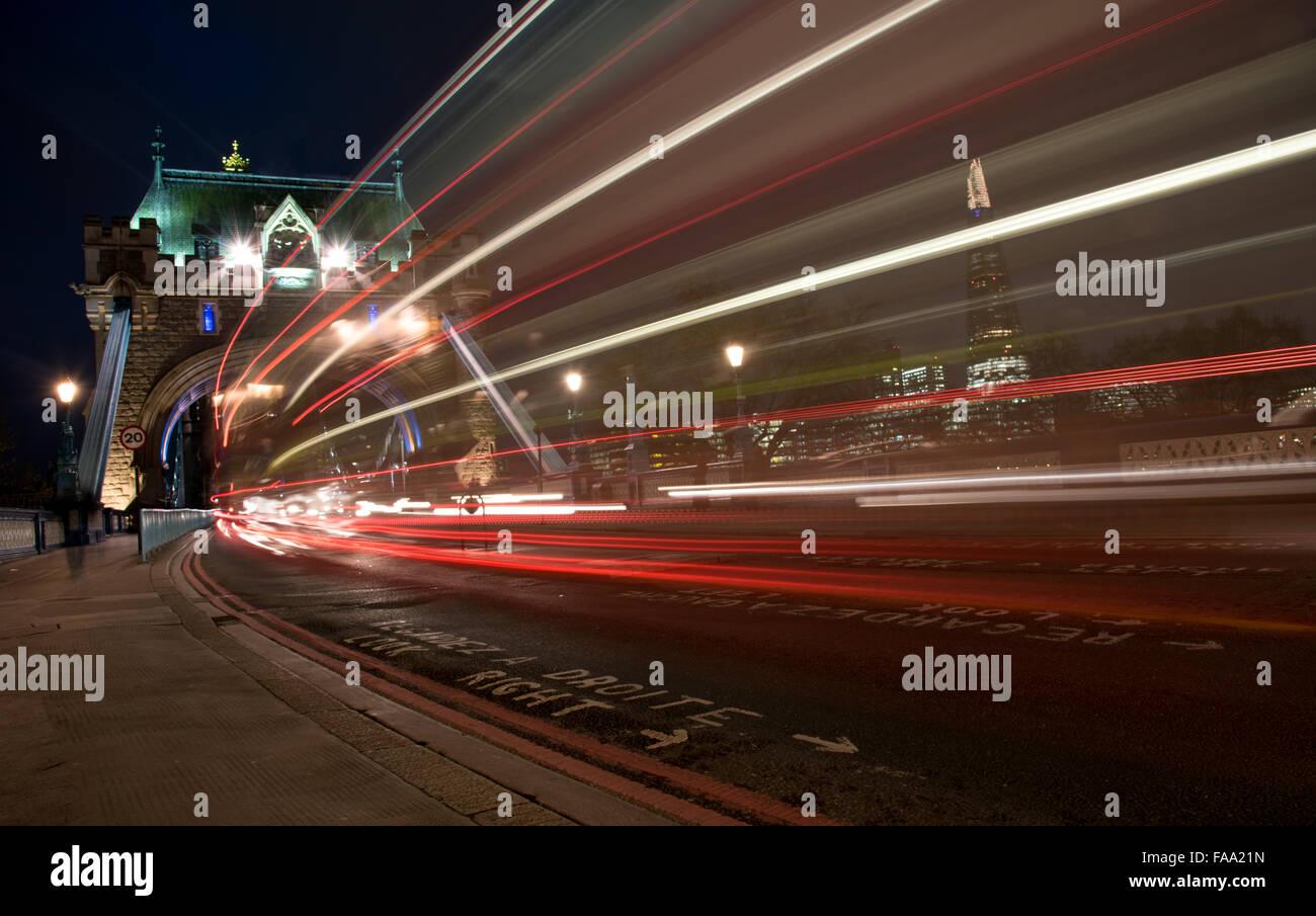 London Tower Bridge, UK, in der Nacht mit Autos und Bussen bunte leichte Spuren zu hinterlassen. Stockbild