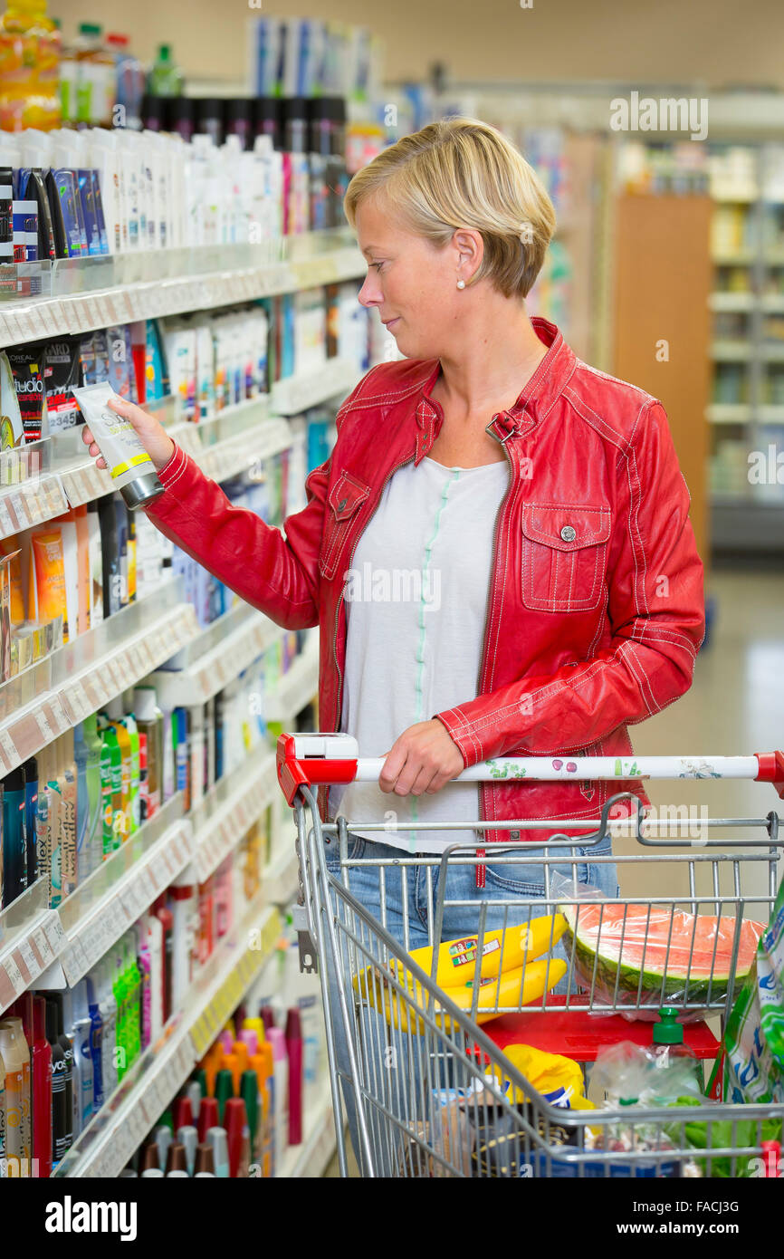 Frau schaut auf ein Produkt im Supermarkt Stockbild