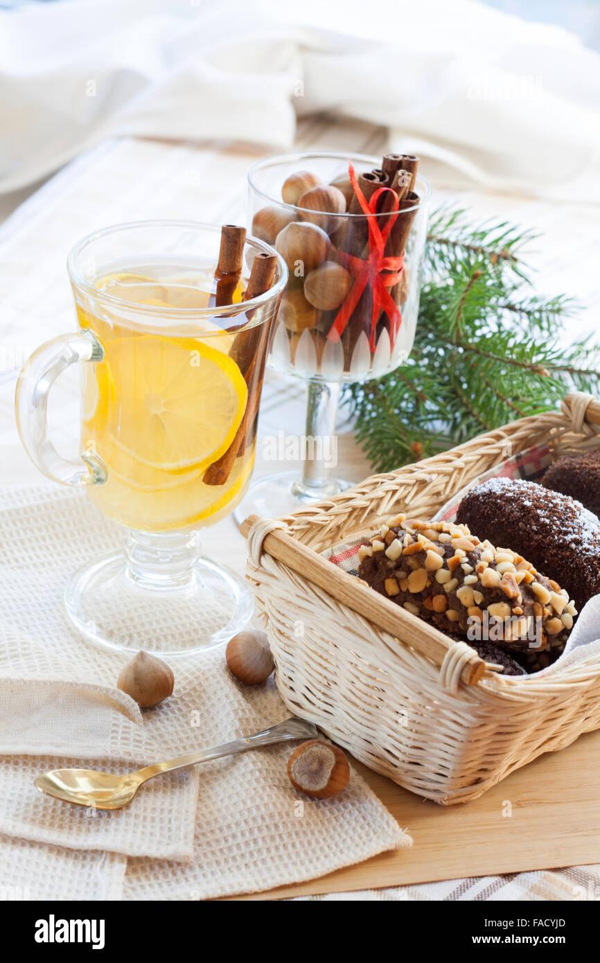 Frische heiße Grüntee in Glasschale mit Zitrone und Zimt, Kuchen Schokolade in Korb und Nüssen und Stockbild