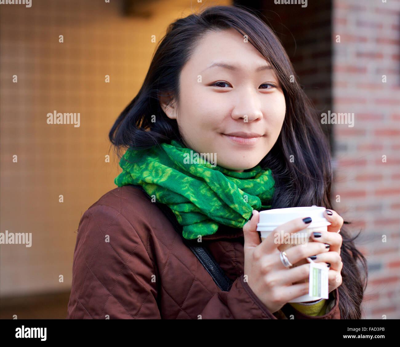 Junge asiatische Frau lächelt in die Kamera, während ihre Hände mit Tee in einen Pappbecher in den Winter-Straßen Stockfoto
