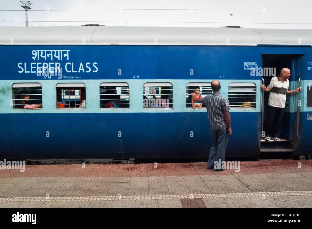 Menschen außerhalb einer Schläfer Serviceklasse Indien Eisenbahn. Stockfoto