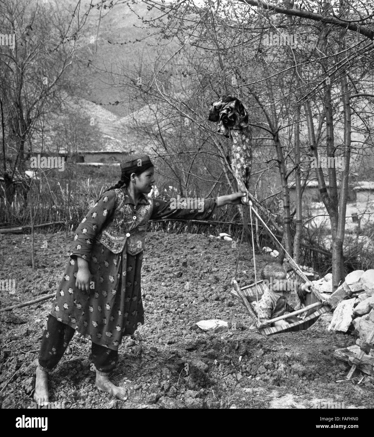 Eine Mutter Schaukelt Ihr Kind Bei Samarkand in Usbekistan Bezirkshandstempel, 1970er Jahre. Eine Mutter, schwingen Stockbild