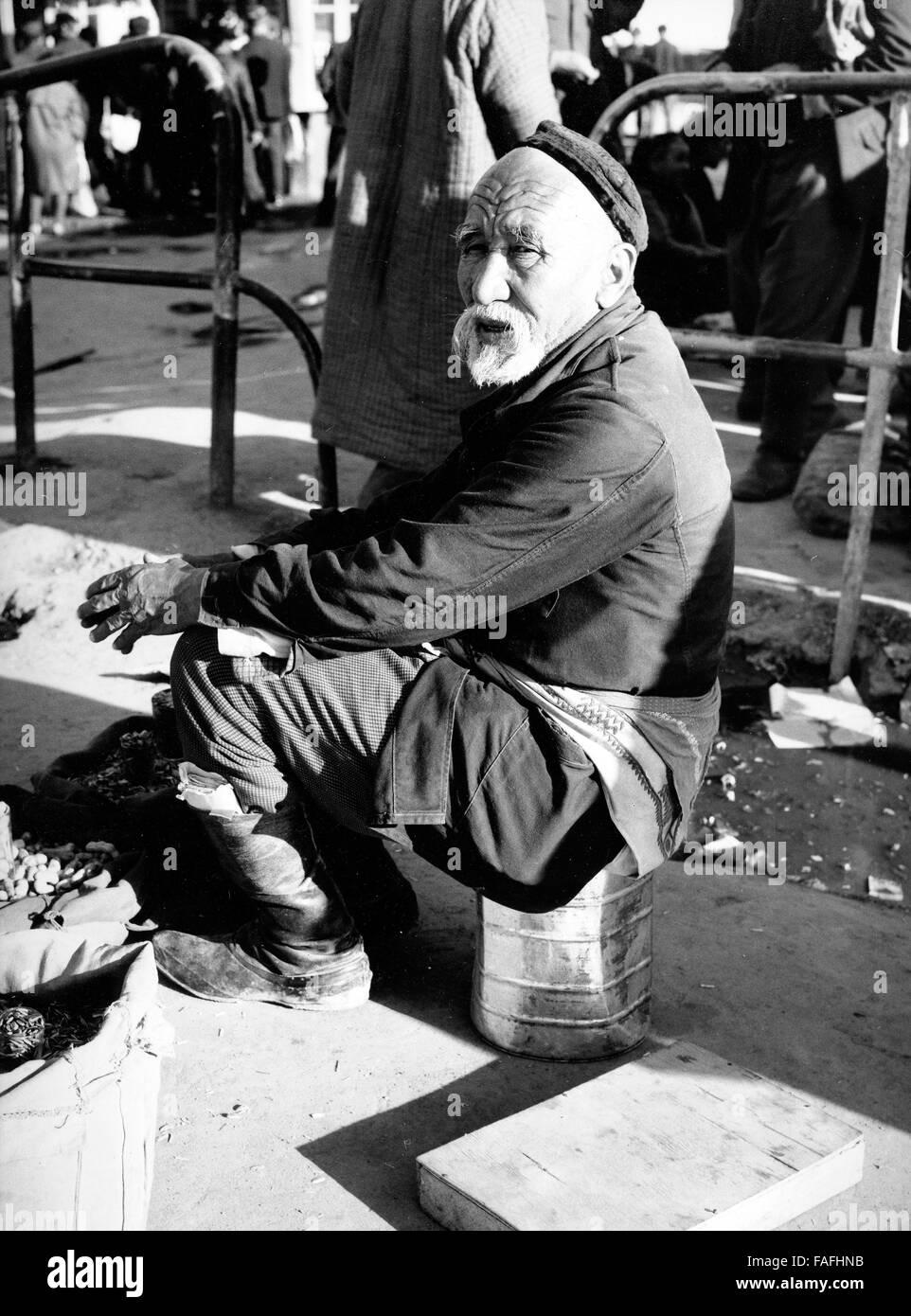 Ein Mann Sitzt Hinter seit Verkaufsstand Auf Dem Basar in Taschkent in Usbekistan, Bezirkshandstempel, 1970er Jahre. Stockbild