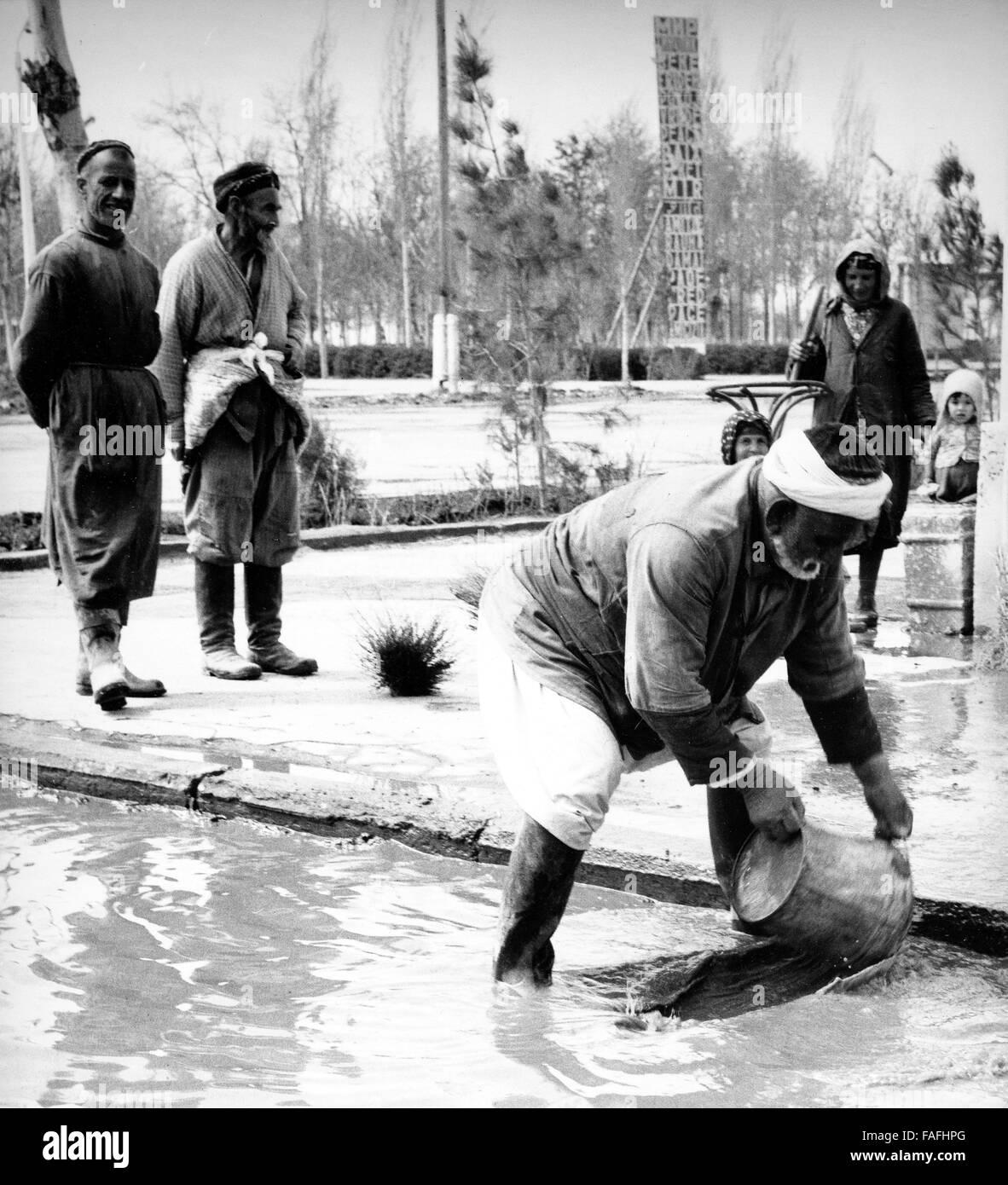 Ein Mann Schöpft Wasser Nach Einem Regenguss in Buchara in Usbekistan, Bezirkshandstempel, 1970er Jahre. Ein Stockbild