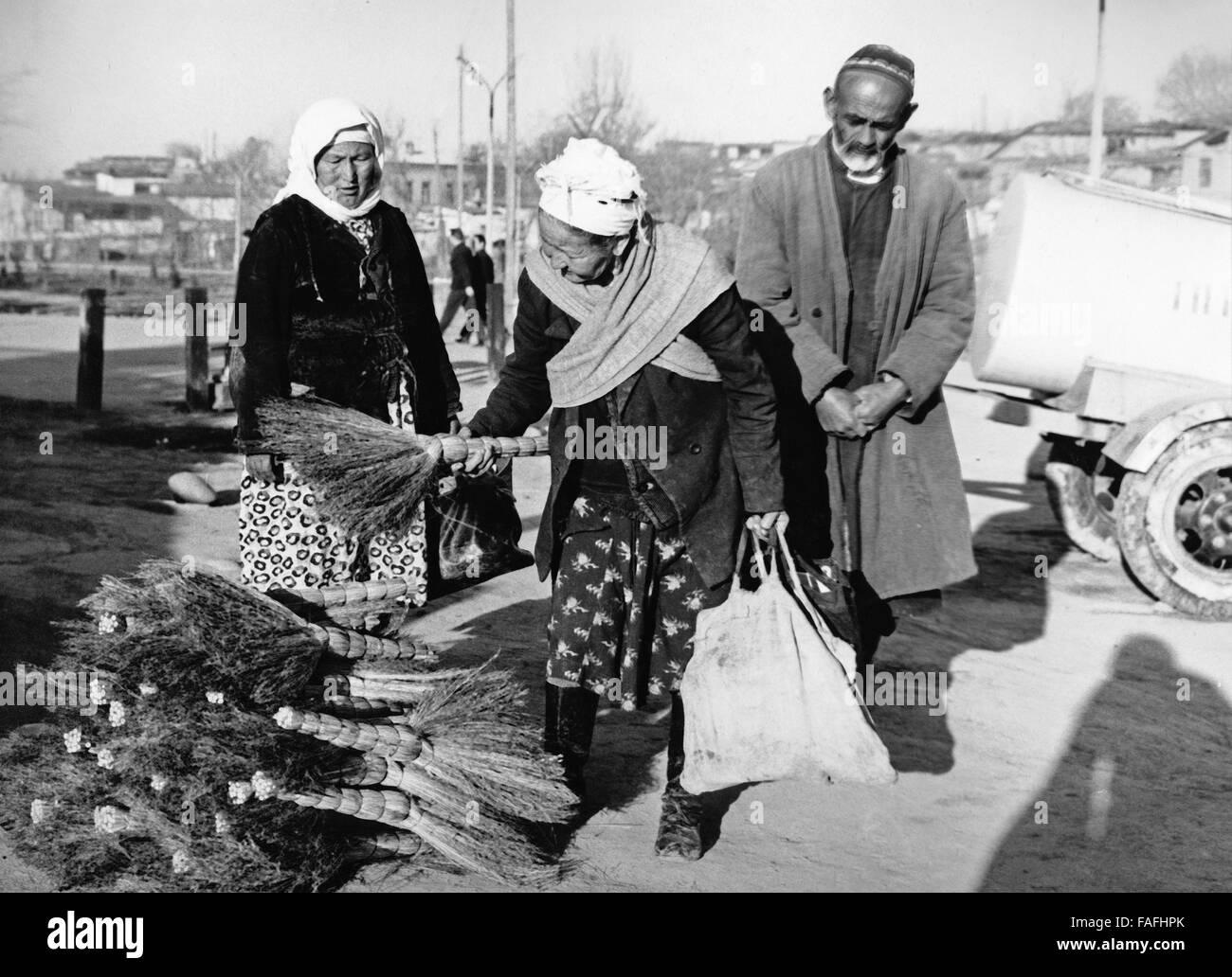 Ein Besenverkäufer Mit Kundin ein seit Stand Auf Dem Basar in Taschkent in Usbekistan, Bezirkshandstempel 1970er Stockbild