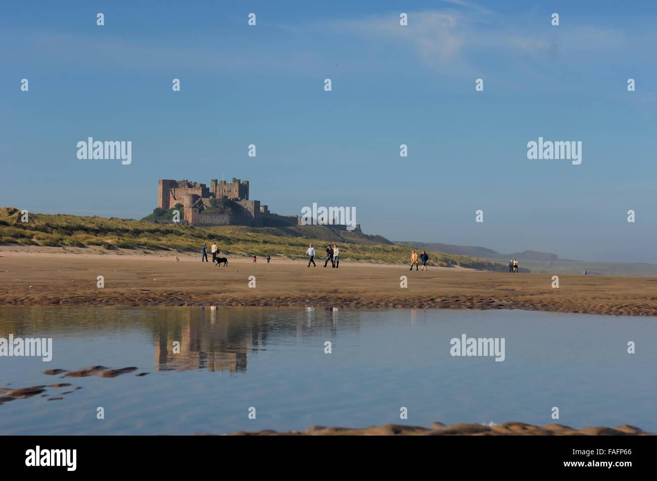 Am Meer spazieren Bamburgh Strand mit Bamburgh Castle im Hintergrund. Northumberland. England. UK Stockbild