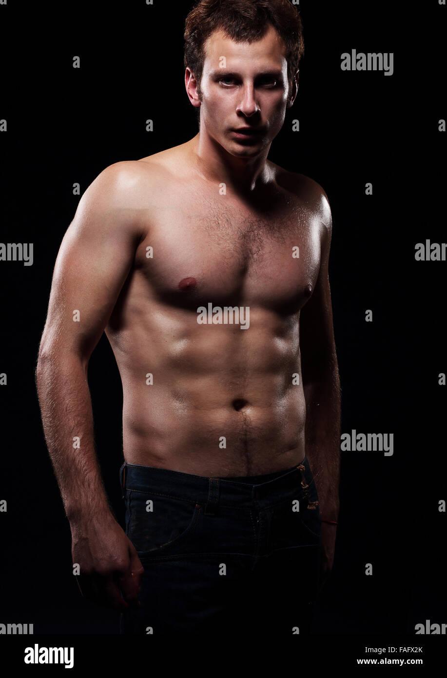 Der schöne und starke junge Mann.  Foto-Shooting im Studio, dunklen Hintergrund. Stockbild