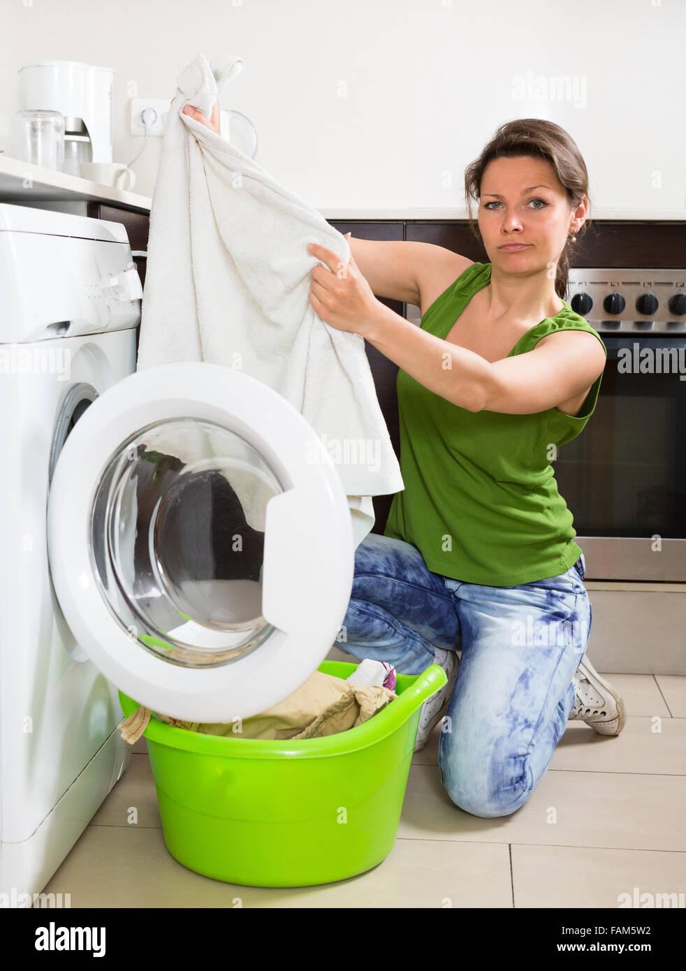 m de junge frau in jeans die waschk che mit waschmaschine in der k che zu hause zu tun. Black Bedroom Furniture Sets. Home Design Ideas