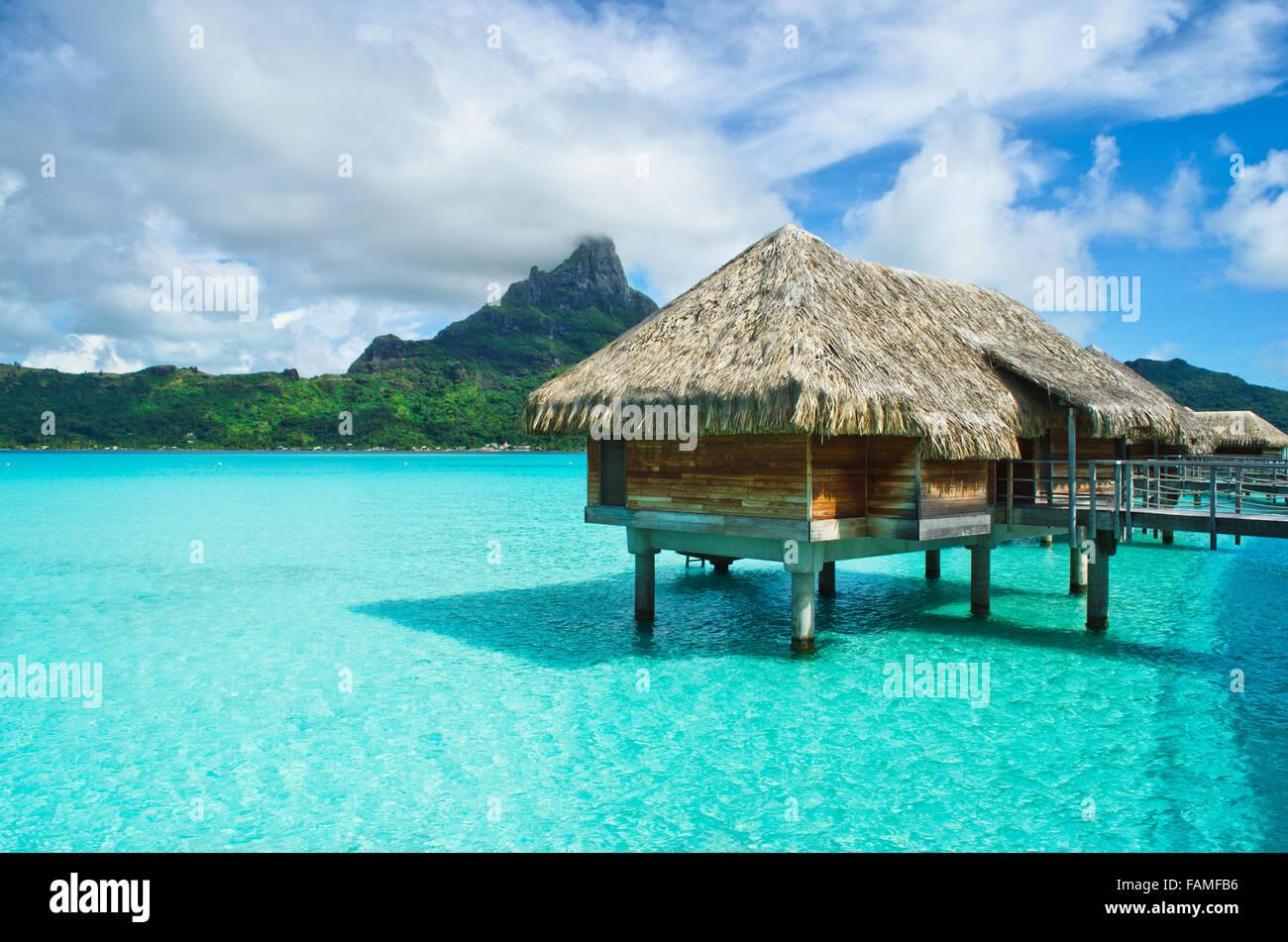 Luxus Overwater strohgedeckten Dach Bungalow in einem Flitterwochen-Urlaub-Resort in der kristallklaren Lagune von Stockbild