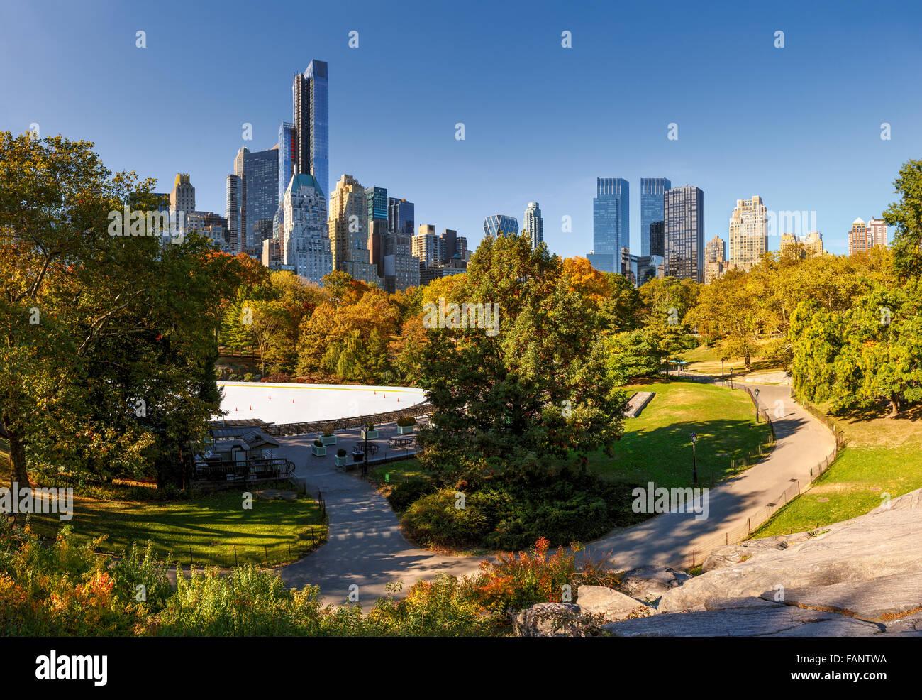 Fallen im Central Park: Wollman Rink und Manhattan Wolkenkratzer. Stadtbild Herbst Blick auf Central Park South, Stockbild