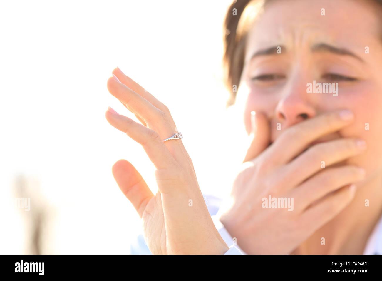 Frau beim Betrachten eines Verlobungsrings nach Vorschlag an einem sonnigen Tag weinen Stockbild