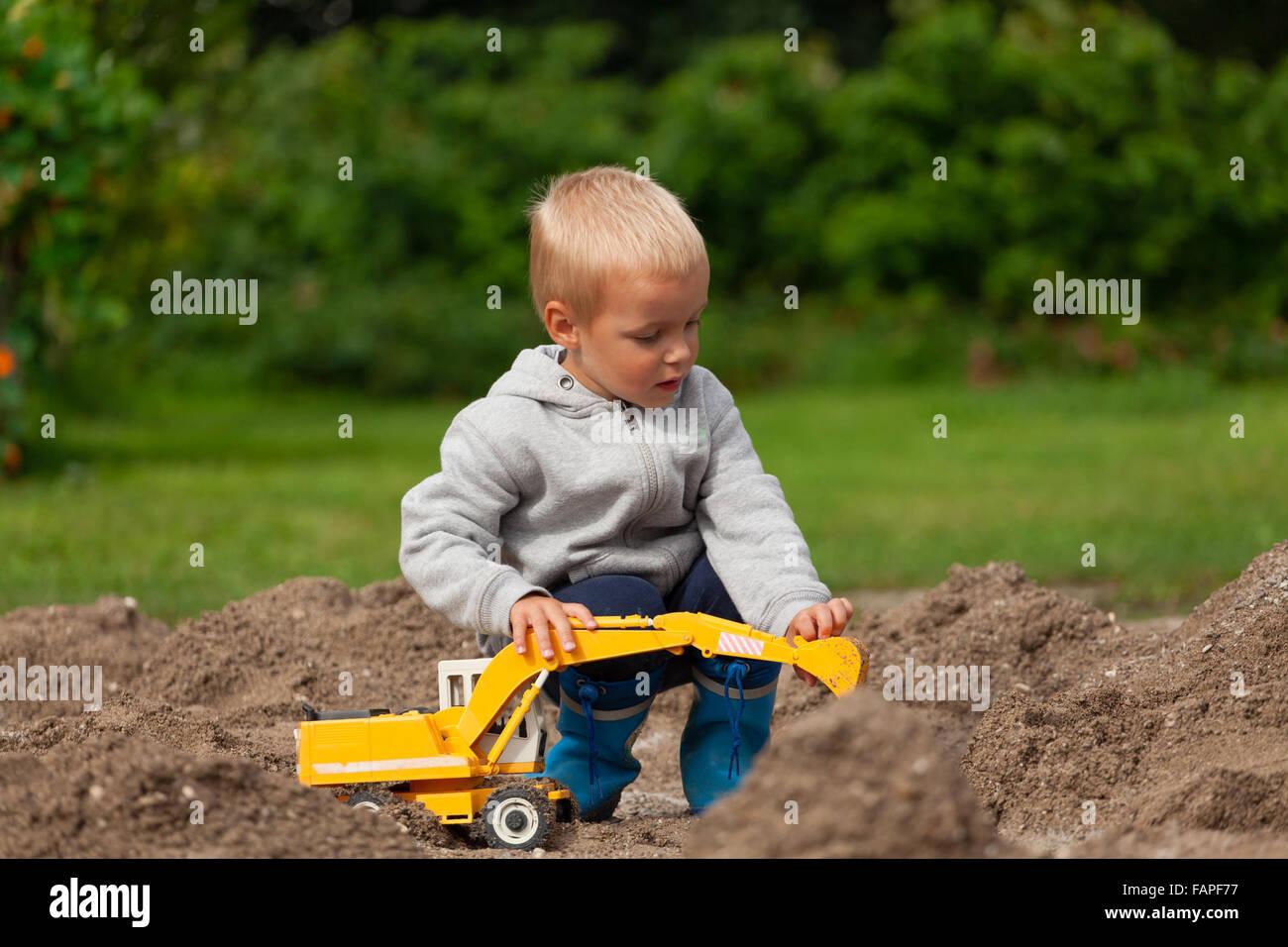 kleiner junge mit kinder bagger im sandkasten spielen stockfoto