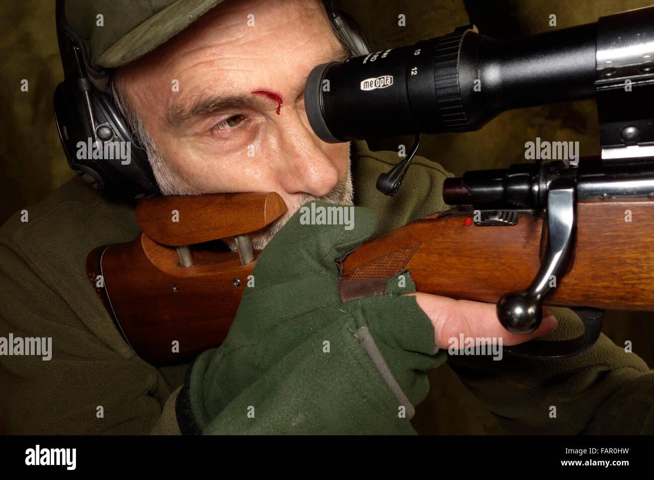 """Ein Jäger mit """"Umfang Auge"""" Wunde schießen eine Gewehr mit Zielfernrohr. Stockbild"""