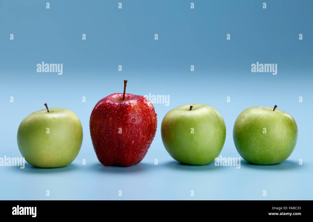 Unterschiedliche Konzepte - roter Apfel zwischen grünen Äpfeln Stockbild