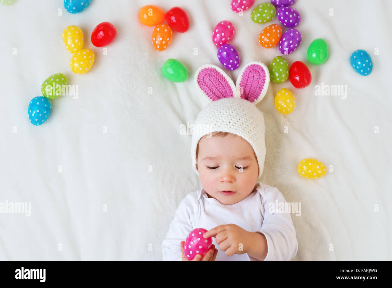 Baby Boy in Hase Hut auf grüne Decke liegend mit Ostereiern Stockbild