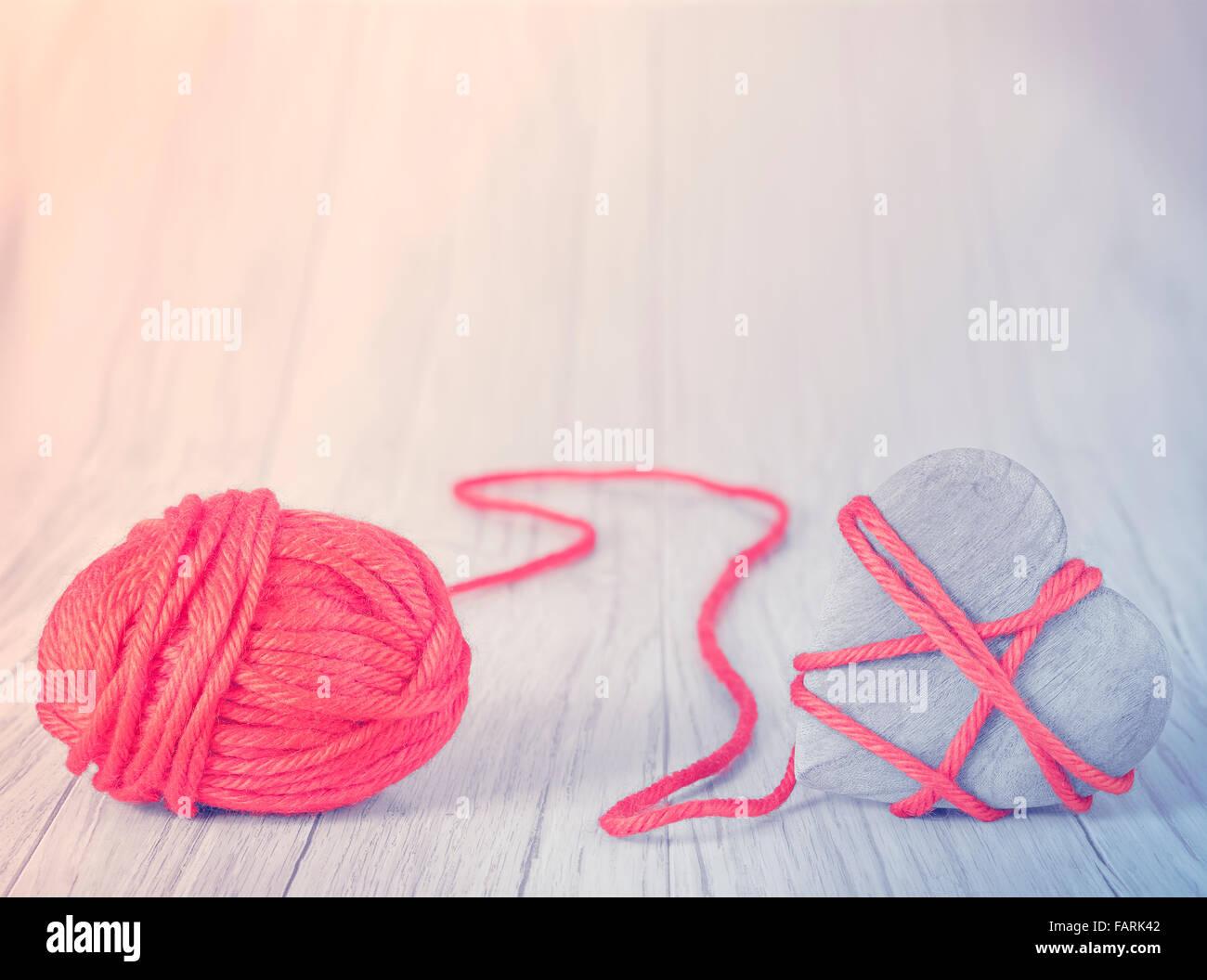 Herz aus Holz mit rotem Garn, Konzept Bild gebunden. Stockbild