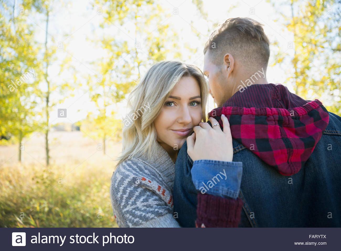 Porträt lächelnde Frau umarmt Freund im Feld Stockbild
