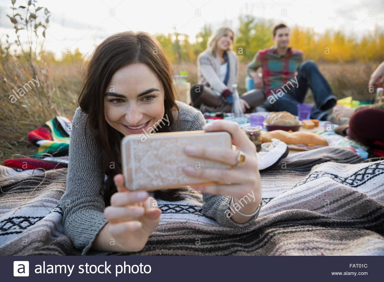Junge Frau, die die Selfie auf der Picknickdecke im Feld Stockfoto