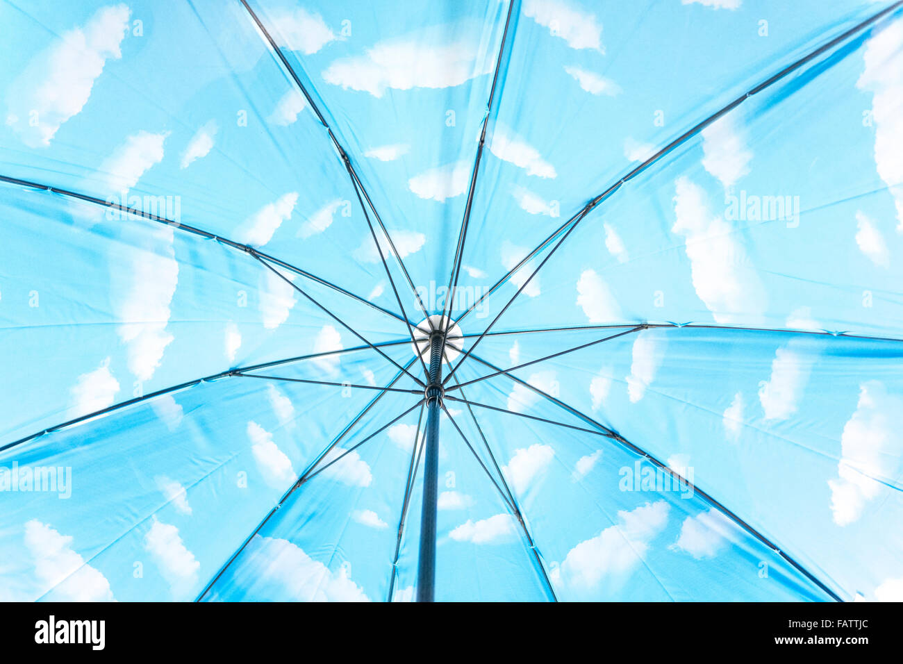 Im Inneren einen Regenschirm mit weißen Wolken am blauen Himmel. Ein Verweis auf Magritte oder Optimismus und Stockbild