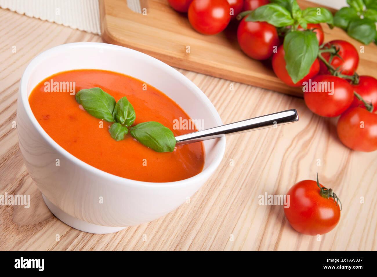 Tomatensuppe mit Basilikum in eine Schüssel geben. Stockbild