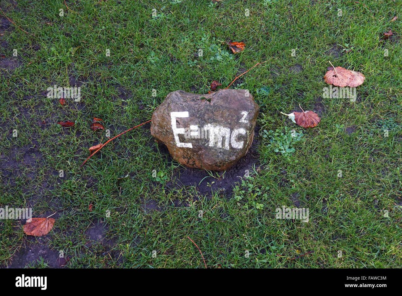 """Die Formel """"E = mc2"""", die Masse – Energie-Äquivalenz, steht auf einem Stein, der auf dem Rasen, fotografiert im Herbst in Nieblum auf Föhr Insel (Schleswig-Holstein), Deutschland, 20. November 2015 liegt. Foto: Jens Kalaene - kein Draht-Dienst- Stockfoto"""